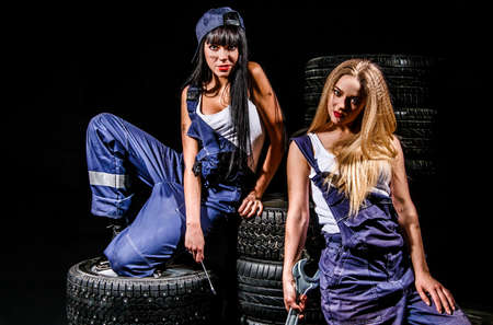 boilersuit: Sexy young women sitting on a tires over black background
