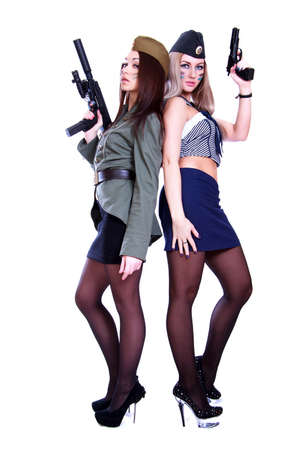 Two women in a vintage military uniforms with guns isolated over white background