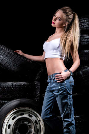 Pretty young woman near the wheels over black background