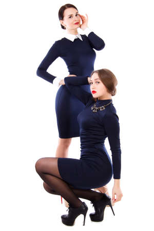 Two young women in a short dark blue dress isolated over white background