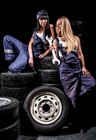 Sexy young women with a big wrench in a tire service over black background