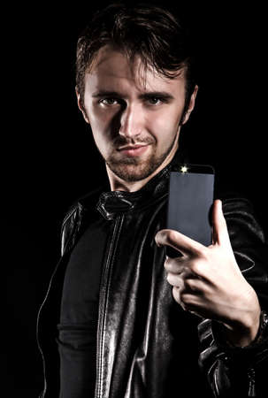 uncombed: Stylish young man taking a selfie over black blackground Stock Photo