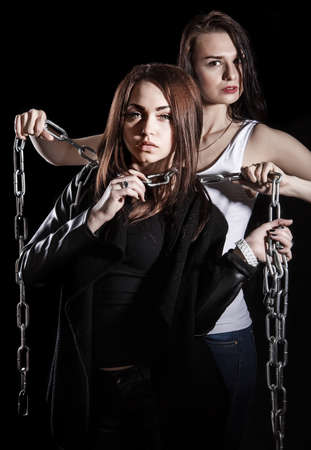 stifle: Beautiful young woman smothers the other one with chains over black background