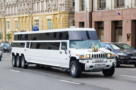 garish: MOSCOW, RUSSIA - JUNE 2, 2013: White luxury limousine Hummer H2 in the city street.