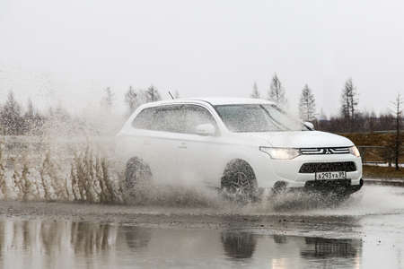 NOVYY URENGOY, RUSSIA - MAY 31, 2016: Motor car Mitsubishi Outlander in the city street during a strong flood.