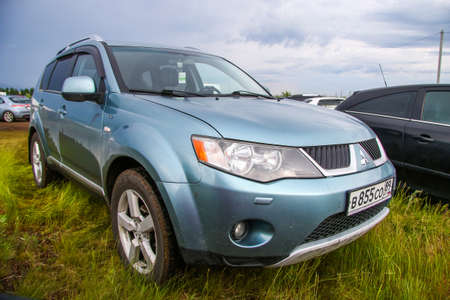 NOVYY URENGOY, RUSSIA - JUNE 25, 2016: Motor car Mitsubishi Outlander at the countryside.