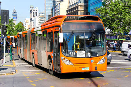 outside machines: SANTIAGO, CHILE - NOVEMBER 13, 2015: Orange articulated city bus Marcopolo Gran Viale in the city street. Editorial