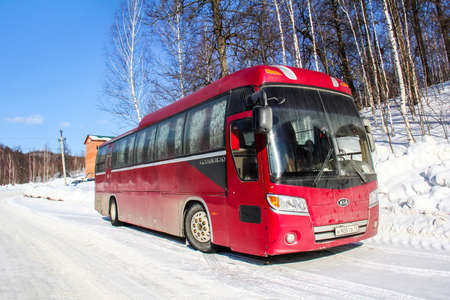 intercity: ASHA, RUSSIA - FEBRUARY 21, 2016: Red intercity coach Kia Granbird at the countryside.