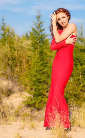 Lady in a red dress in the summer forest