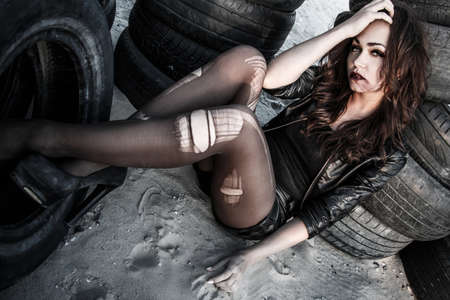 torn stockings: Disheveled redhead woman between an old tires