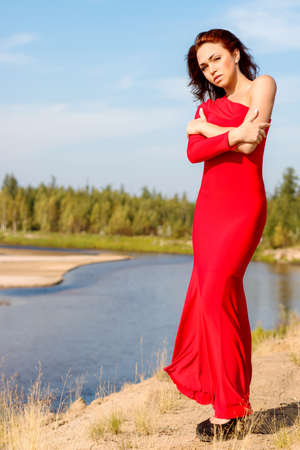 oneself: Lady in a red dress staying on the river edge Stock Photo