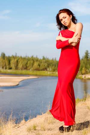 suelo arenoso: Señora en un vestido rojo que permanece en la orilla del río