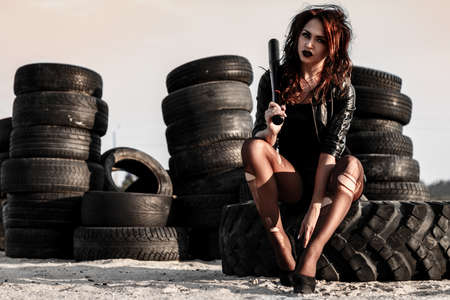 Disheveled redhead woman sitting with a baseball bat at the background of an old tires Stock Photo