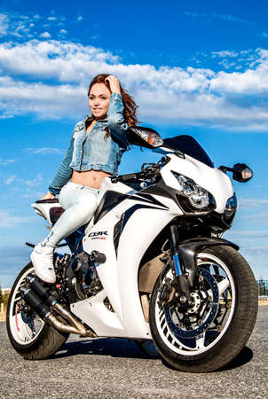 NOVYY URENGOY, RUSSIA - AUGUST 21, 2016: Cute young woman sitting on the white bike Honda CBR-1000RR.