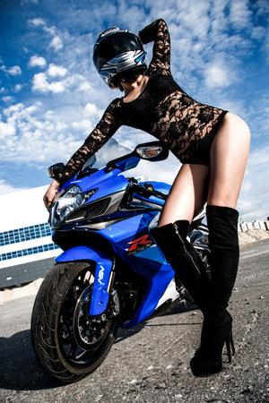 NOVYY URENGOY, RUSSIA - AUGUST 21, 2016: Sexy young woman in the Shoei helmet staying near the dark blue bike Suzuki GSX-R750. Editorial