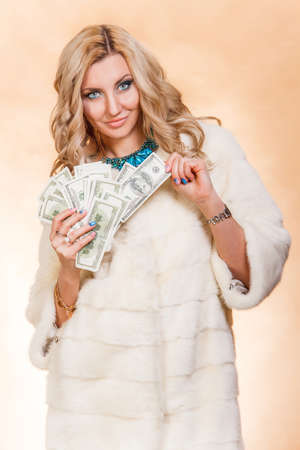 covetous: Young woman in a fur coat holding money over golden background