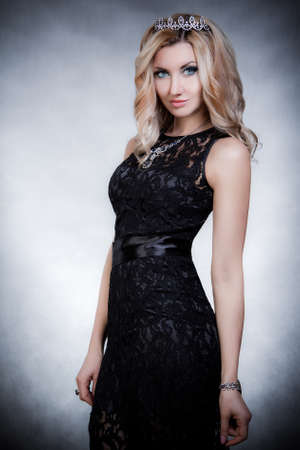 Beautiful young woman in a crown and a black evening dress
