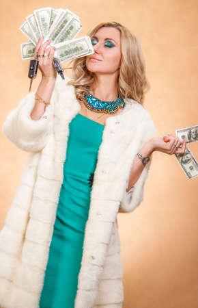 éxtasis: Mujer joven en un abrigo de piel que sostiene el dinero sobre fondo de oro