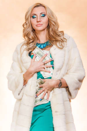 avid: Young woman in a fur coat holding money over golden background