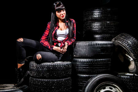 Young woman in a red checked shirt sitting on a tires over black background