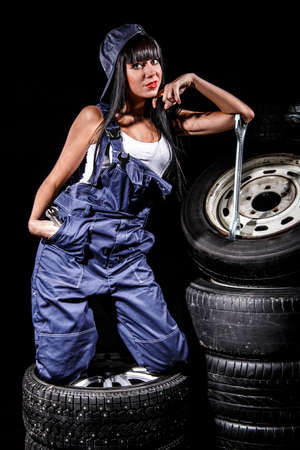 boilersuit: Sexy young woman with a big wrench in a tire service over black background