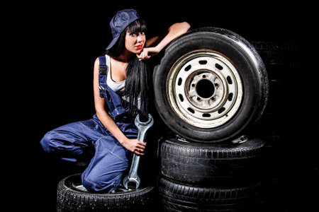 Cute young woman sitting on a tires with a big wrench over black background Stock Photo