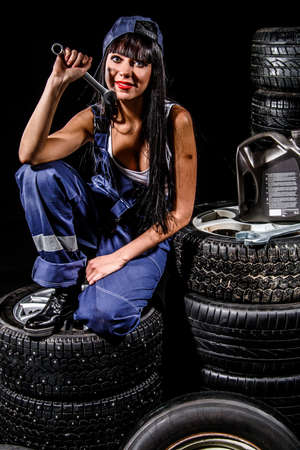 boilersuit: Sexy young woman sitting on a tires over black background Stock Photo