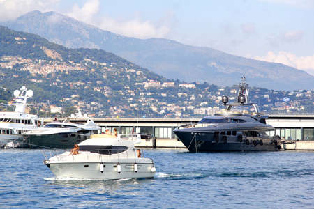 super yacht: MONTE CARLO, MONACO - AUGUST 2, 2014: Luxury yachts at the background of the city architecture.