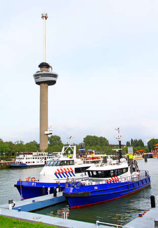 euromast: ROTTERDAM, NETHERLANDS - AUGUST 9, 2014: View of the observation tower Euromast and two police boats at the evening.