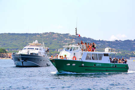 tropez: SAINT-TROPEZ, FRANCE - AUGUST 3, 2014: Green ferry boat Gipsy IX and a black luxury yacht at the city bay.