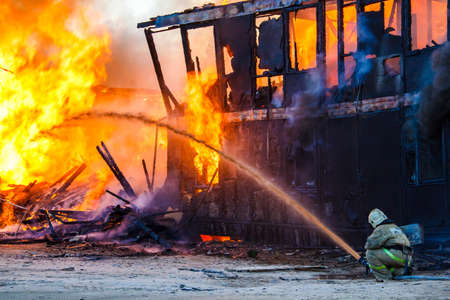 Fireman extinguishes a burning old wooden residential house