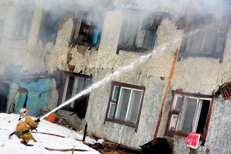 burning house: NOVYY URENGOY, RUSSIA - MAY 9, 2015: Fireman extinguishes a burning old wooden residential house.