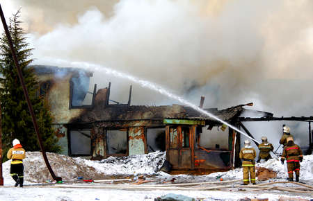 NOVYY URENGOY, RUSSIA - MAY 9, 2015: Old wooden residential house burns with a grey smoke and heavy flames. Editorial