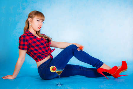 Beautiful young woman sitting on a floor with a cocktail over cyan background Stock Photo