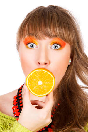 Cute young woman with an orange fruit in a mouth isolated over white background