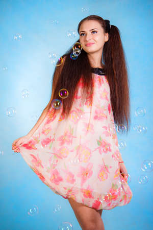Cute young woman with soap bubbles over cyan background Stock Photo