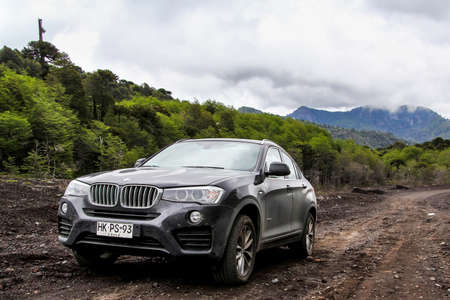 ARAUCANIA, CHILE - NOVEMBER 22, 2015: Black crossover BMW F26 X4 at the dirt road near the Llaima volcano.