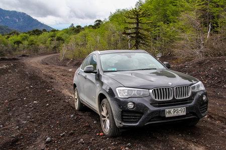 ARAUCANIA, CHILE - NOVEMBER 22, 2015: Black crossover BMW F26 X4 at the dirt road near the Llaima volcano.