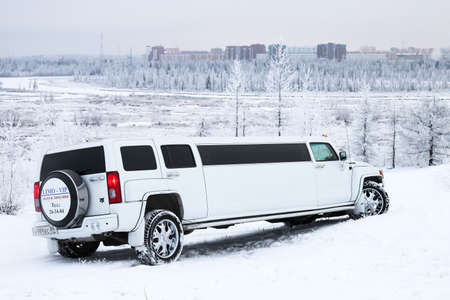 snow covered forest: NOVYY URENGOY, RUSSIA - OCTOBER 21, 2016: White limousine Hummer H3 in the snow covered forest.
