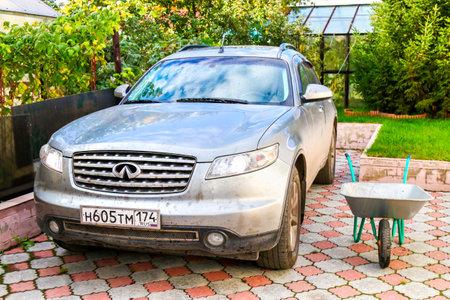CHELYABINSK, RUSSIA - OCTOBER 2, 2016: Grey motor car Infiniti FX35 in the small garden. Editorial