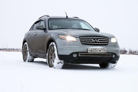 super cross: Novyy Urengoy, Rusia - 20 octubre 2016: Gris automóvil Infiniti FX35 en la tundra cubierta de nieve. Editorial