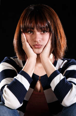 Unhappy young girl over black background Stock Photo