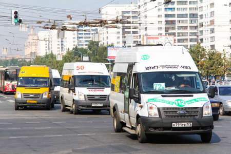 fixed line: CHELYABINSK, RUSSIA - JULY 18, 2012: Small city buses Ford Transit in the city street.