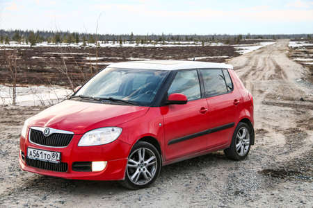 affordable: NOVYY URENGOY, RUSSIA - MAY 20, 2016: Red car Skoda Fabia SE at the background of a swamp. Editorial