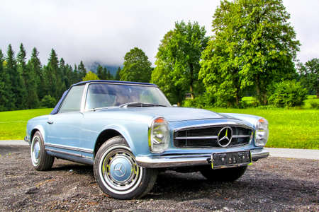 TYROL, AUSTRIA - JULY 29, 2014: Cyan retro car Mercedes-Benz W113 230SL in the small high Alpine village.