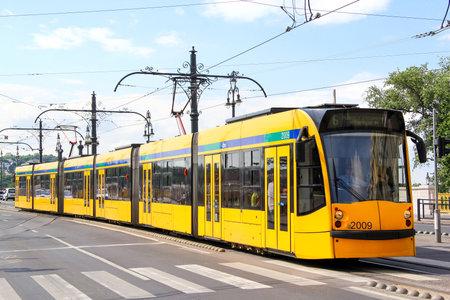 BUDAPEST, HUNGARY - JULY 23, 2014: Yellow articulated tramway Siemens Combino Supra NF12B in the city street.