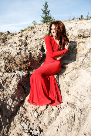 oneself: Lady in a red dress sitting in the dirt Stock Photo