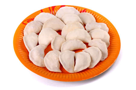 Frozen vareniki laying on the orange plate isolated over white background
