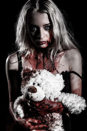 Bloody young woman holding a teddy bear over black background Фото со стока