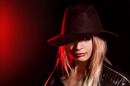 uncombed: Portrait of a pretty young girl in a big hat over red and black background Stock Photo